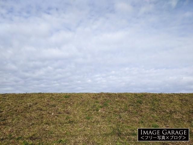 下から見た川の土手とうろこ雲の空のフリー素材写真(無料)