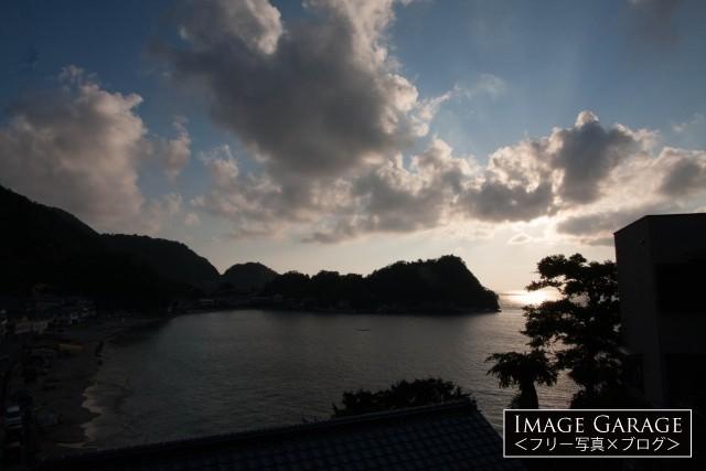 逆光の中の素朴な岩地海岸のフリー写真素材