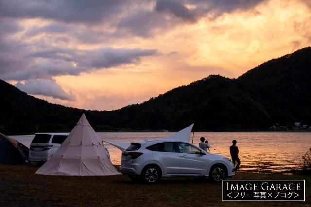 西湖自由キャンプ場で夕焼けを眺めるキャンパーのフリー素材写真(無料)