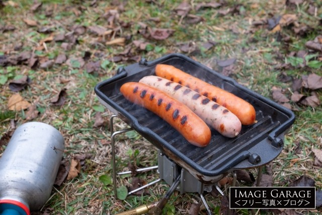 ソロキャンプ用のグリルプレートで焼いたソーセージのフリー素材写真(無料)