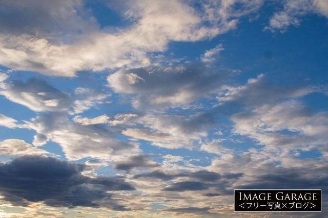 青空と雲のコントラストが美しい夕方の空(横位置)のフリー素材写真(無料)
