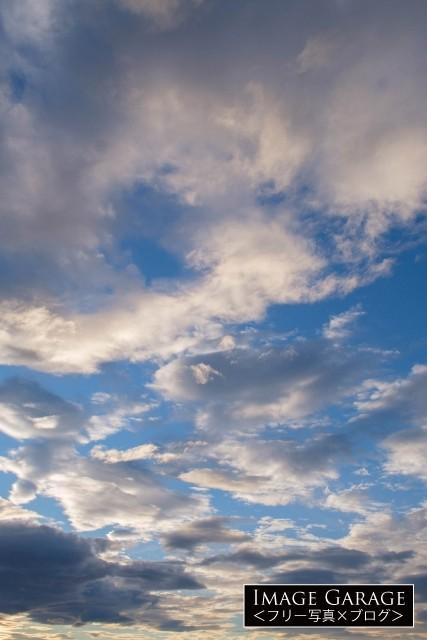 青空と雲のコントラストが美しい夕方の空(縦位置)のフリー素材写真(無料)']