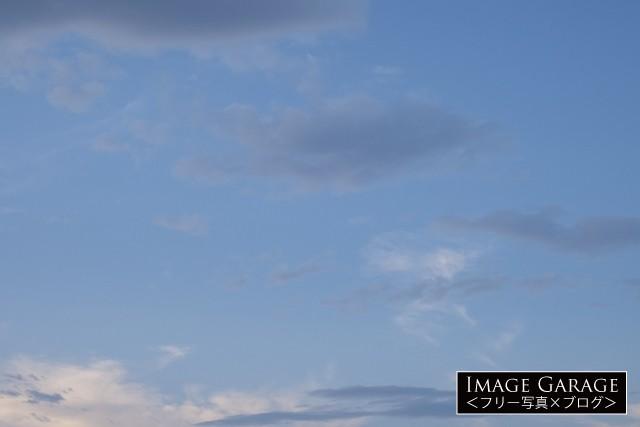 グレーの雲がかかった明暗差の少ない青空のフリー素材写真(無料)