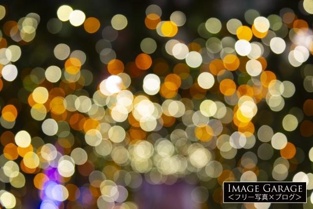 キラキラしたクリスマスイルミの玉ボケ背景のフリー写真素材