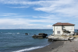砂浜の上の岩に建つ、限りなく海に近い家