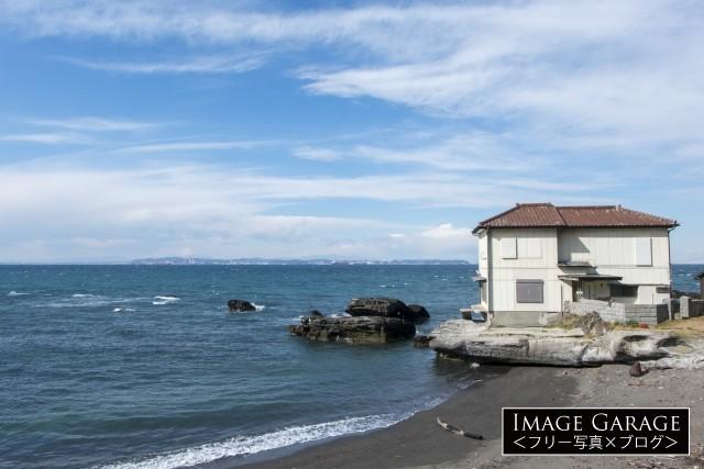 砂浜の上の岩に建つ限りなく海に近い家のフリー写真素材(無料)