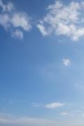 下に小さめ上に大きめの雲がある青空(縦)