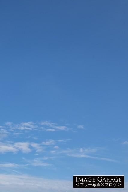 下の方にだけ少し雲がある縦位置の青空の無料写真素材(無料)