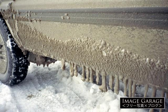 道路上の水が付着しウロコ状に凍った車の外装のフリー写真素材