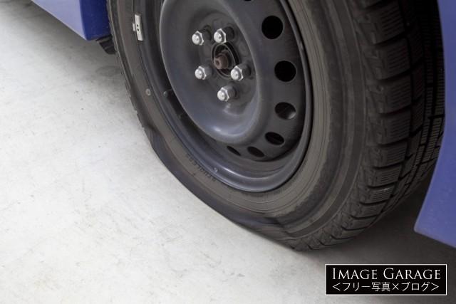 パンクした車のタイヤのフリー写真素材(無料)