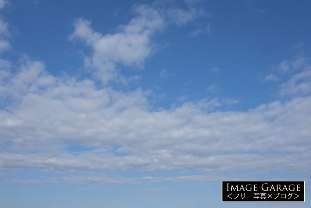 真ん中に雲が密集している青空(横位置) のフリー写真素材(無料)