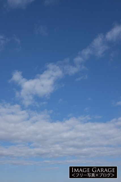 真ん中に雲が密集している青空(横位置)のフリー写真素材(無料)