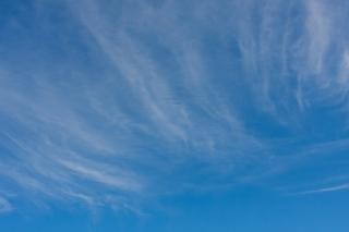 濃い目のスジのような雲がある青空