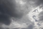 黒い雲が覆いながら光が差し込む曇り空