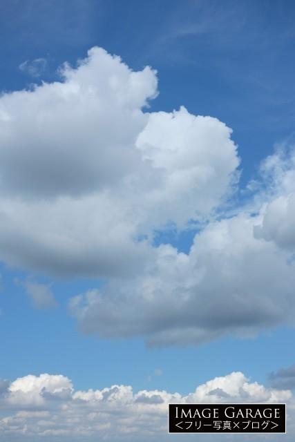 大きな雲の浮く青空(縦)のフリー写真素材(無料画像)