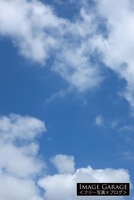 斜め上に見上げた青空(縦位置)のフリー写真素材(無料画像)