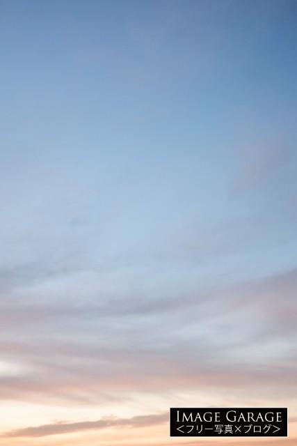 うっすらオレンジがかった青空(縦位置)のフリー写真素材(無料画像)
